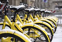 Detail of yellow bikes in Milan after snowfall, Milan, Lombardy, Italy, Europe.