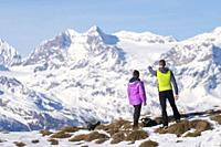 .Couple of hikers admire the Swiss mountains from Monte Padrio, Corteno Golgi, Province of Brescia, Lombardy, Italy, Europe