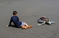 Kid sits next to dead hawksbill sea turtle (Eretmochelys imbricata) killed by boat propeller in Ladrilleros, Pacific Coast of Colombia.