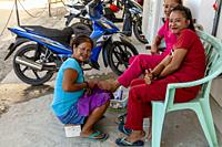 A Local Woman Has A Pedicure In The Street, El Nido, Palawan, The Philippines.
