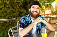 portrait of happy young man with beard and headscarf while having a soda on a terrace.