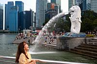 Singapore, Republic of Singapore, Asia - A female tourist poses for photos in the Merlion Park along the Singapore River with the Central Business Dis...