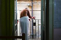 Syracuse, Ortegia, Sicily, Italy A man wearing a towel holds a coffee pot on the balcony.