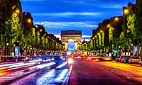 Illuminated Champs Elysee and view of Arc de Triomphe in parisian evening, France.