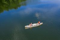 Prairieville, Michigan - Two women with a small child paddle a canoe on Stewart Lake.