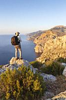 South sector of the Serra de Tramuntana and S'Evangelica mountain with hiker, Andratx, Majorca, Spain.