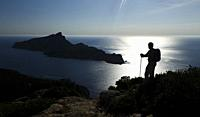 Backlight view of the island of Sa Dragonera from Andratx coast with hiker, Mallorca, Spain.