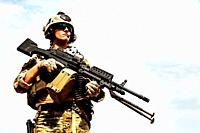 Low angle portrait of US Army Ranger with machinegun on blue sky background looking up. National pride concept.