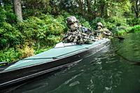 Special forces men with painted faces in camouflage uniforms paddling army kayak. Boat moving across the river, diversionary mission, diagonal view.