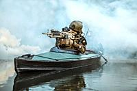 Special forces marine operators in camouflage uniforms paddling army kayak through river fog. Diversionary mission, machine gunner ahead.
