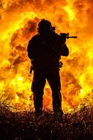 Backlit silhouette of special forces marine operator in forest on fire explosion background. Battle, bombs exploding, fighting no matter what.