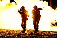 Black silhouettes of pair of soldiers in the smoke fire burning moving in battle operation. Back light.