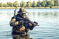 Bearded soldier of special forces in action during river raid in the jungle terrain. He is waist deep in the water and mud and ready to meet enemy, su...