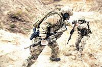 US ranger, modern infantryman, special reconnaissance team member or military scout in ammunition, armed with service rifle helping brother in arms to...