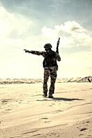 Soldier of special forces, infantry rifleman in military ammunition walking in desert and pointing on horizon. Military reconnaissance team leader man...