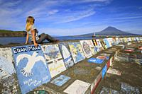 Woman sitting at the port of Horta observes Pico Island, Marina da Horta, Cais de Santa Cruz, Faial, Azores, Portugal, Western Europe.