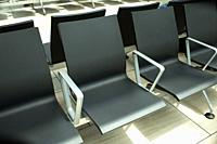 Empty chairs in an airport terminal.