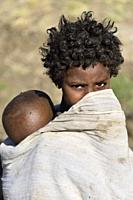 Ethiopia, Amhara region, Dabat village, Shy girl carrying her little brother.