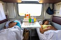Man and woman sleep on lower shelves in a train car.