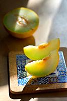 Melon with slices on a wooden table.
