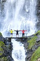 Three hikers holding hands in waterfall of Ardones, Cerler, Huesca, Aragon, Spain