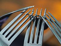 VClose up of a group of silver shiny forks.