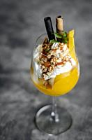 organic mango and passion fruit tropical ice cream sundae in wine glass.