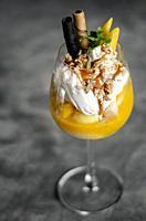 organic mango and passion fruit tropical ice cream sundae in wine glass.