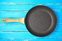 new empty frying pan with a brown handle on a blue wooden background, bottom with a crumb of stone and marble.