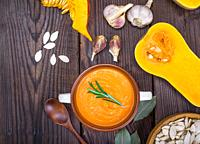 pumpkin soup in a ceramic plate with a wooden spoon on a brown table, next to pumpkin seeds and garlic, empty space on the left.