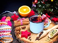 Mulled wine in an iron blue mug and drink ingredients among the Christmas decorations.