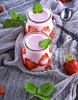 smoothies of fresh strawberries and yogurt in a glass jar on a gray napkin, top view.