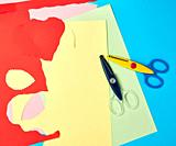 pair of plastic scissors and colored paper for cutting figures, application and scrapbooking.