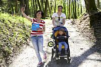 mother taking selfie with family during hiking trip in forest, at Herrenchiemsee Insel, Chiemsee, Bavaria, Germany