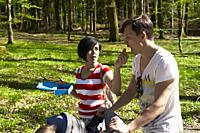 women feeding husband with healthy carrot during hiking trip in forest, at Herrenchiemsee, Chiemsee, Bavaria, Germany