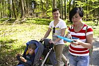 parents with buggy and toddler child walking in forest, at Herrenchiemsee, Chiemsee, Bavaria, Germany