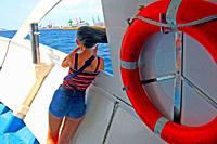 girl and life buoy on the deck of tourist cruise, maritime facade of Barcelona, ??Catalonia, Spain