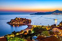 Sveti Stefan island in Montenegro, sunset on the seacoast. Popular travel destination.