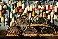 Lobster traps and buoys dominate a seafood restaurantâ. . s exterior walls.