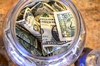 Money in a tip jar in a restaurant.