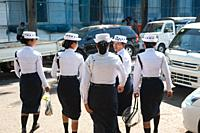 Yangon, Myanmar, Asia - A group of female traffic police officers walks down a road in the centre of the former capital.