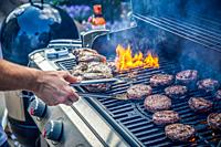 Marinated lamb joint and beef burgers cooking on an outdoor barbecue.