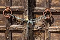 Old wooden door in Tuscany, Italy. Slightly ajar but locked with a modern chain.