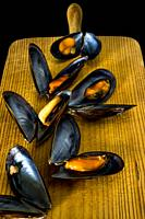 Cooked mussels on a wooden board.