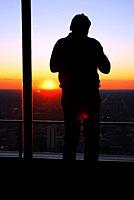 An adult man views the sunset form an observational tower.