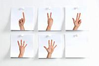 Five white Post It hanging on the wall with images of fingers indicating numbers and an empty one.