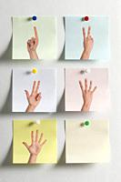 Five colorful Post It messages fixed to the wall with images of fingers indicating numbers and an empty one.