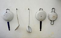 Old kitchenware hang on a wall in Statarmuséet, the museum of farmworker´s home in Torup, Scania, Sweden.