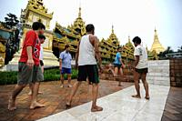 Yangon, Myanmar, Asia - A group of men plays chinlone outside the temple compound of the Shwedagon Pagoda. The game is the Southeast Asian country's n...