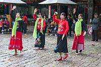 Female folk dancers perform in a town square in the Old Quarter of Lijiang, Yunnan, China.